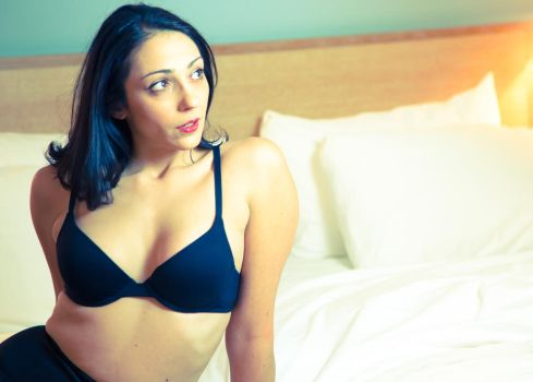 Woman in black bra on bed by Harcom