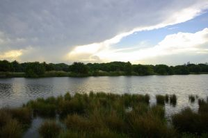 Storm dispersing above lake. by Andrezao