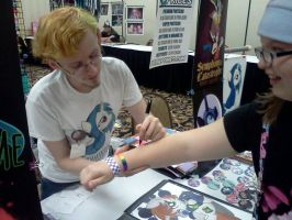 Signing a fan's arm at Cutie Mark Con by drawponies