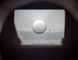 City through the viewfinder of an old SLR camera. by Eevl