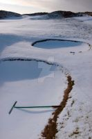 rakes in bunker on a snow covered link golf course by morrbyte