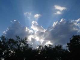 sun through clouds over trees by BANanered